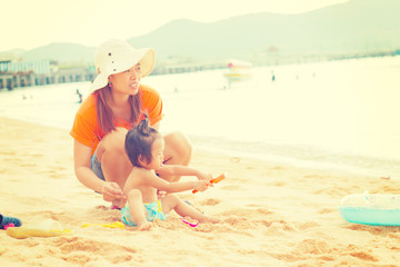 Daughter and mom playing on beach  with retro filter