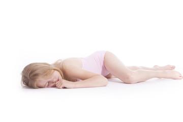 young blond girl sleeping on the floor of studio