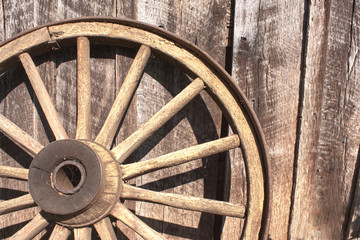Wooden wheel leaning against barn
