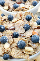Healthy whole grain muesli and bran breakfast with fruits in mil