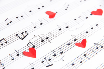 Red paper hearts on music book, close-up