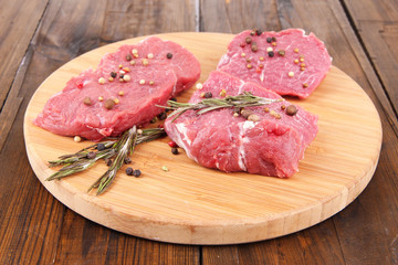 Raw beef meat with spices on cutting board on wooden background