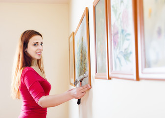 Smiling  woman hanging  picture  on wall