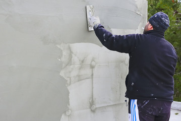 worker plastering facade of high-rise building with putty knife