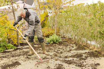 Gardener raking soil