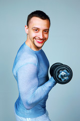 Cheerful man working out with dumbbells over gray background