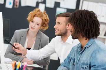 kreatives team im büro schaut auf computer