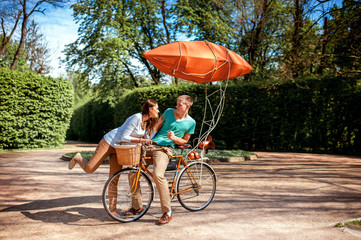 Lovely young couple having fun with the bicycle with red dirigib