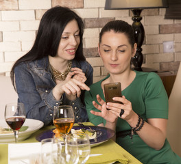 Two women using a smart phone. At restaurant during a dinner
