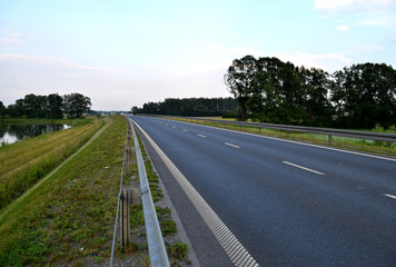 Photo of dark asphalted road and metall barrier