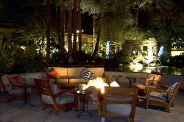 Patio furniture pool side lit up at night