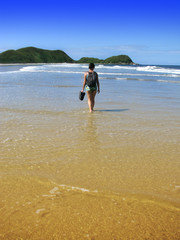 Brazil: Attractive young woman walking in a gorgeous wild beach