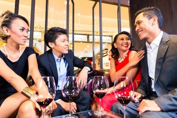 Asian Friends drinking wine in bar