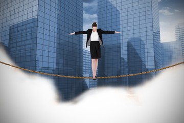 Composite image of businesswoman performing a balancing act