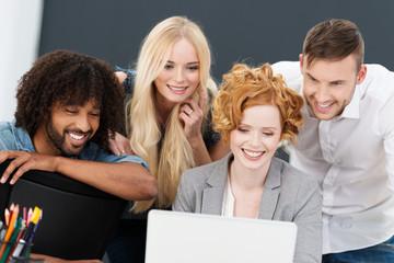 vier junge leute schauen zusammen auf laptop