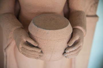 Hands hold alms bowl of buddha statue