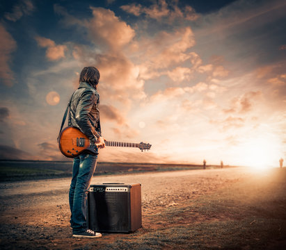 guitarist on a road to sunset