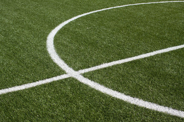 Part of a soccer field with synthetic grass and white lines