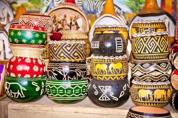 Colorfully painted wooden pots in market,  Africa.