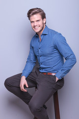 happy young elegant casual man smiling, sitting