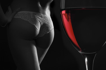 Beautiful silhouette of a female body and a glass of red wine