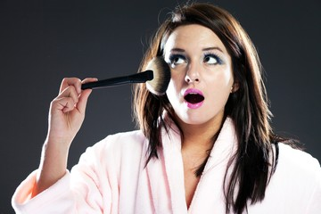 Funny surprised woman in bathrobe and powder brush
