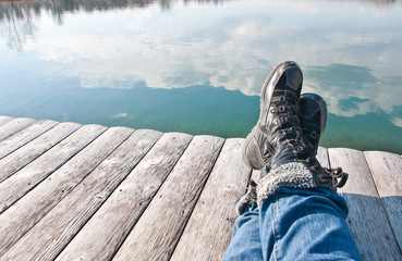 person lying on a boardwalk enjoying the view over the lake