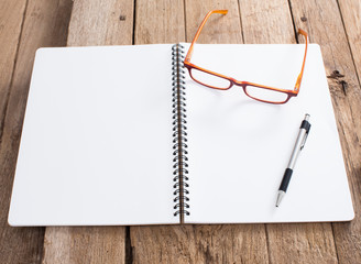 Blank notebook with pen and eyeglasses on old wooden background