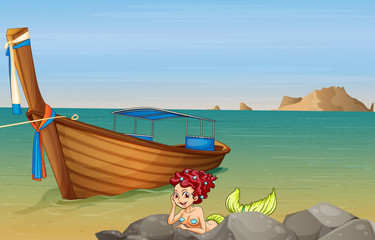 A mermaid at the sea near the wooden boat