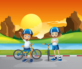 Two kids with their bikes standing at the road near the river