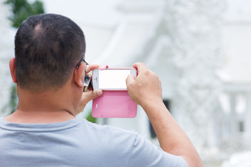fat man taking a photo of a temple in Thailand, with mobile phon