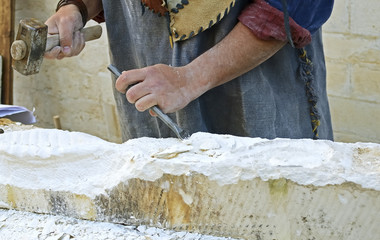 Stonemason working of sandstone with hammer and chisel.