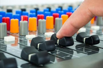 Hand making slide on an audio soundboard