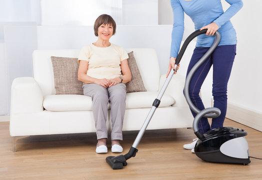Caretaker Cleaning Floor While Senior Woman Sitting On Sofa