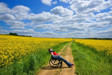 Disabled woman sunbathing on a wheelchair, rape field, spring