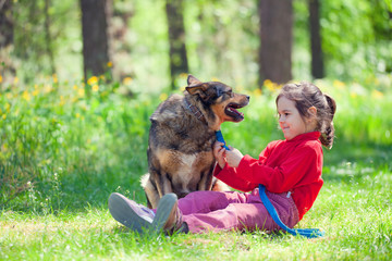 Happy little girl with big dog sitting in the lawn in the forest