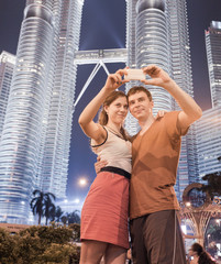 Young couple photographed against two Petronas Twin Towers