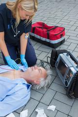 Paramedic examining unconscious patient