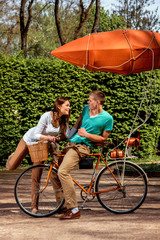 Young and joyful couple having fun in the park with bicycle and