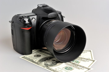 Photo camera with dollars on gray