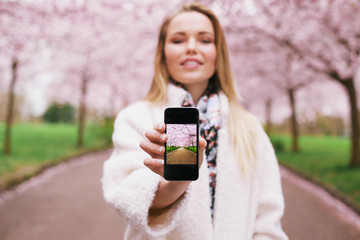 Young lady at spring park showing pictures on her mobile phone