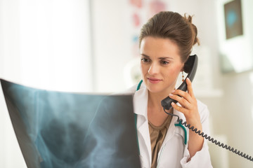 Medical doctor woman looking on fluorography and talking phone