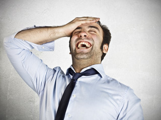 Young businessman laughing with hand on the head