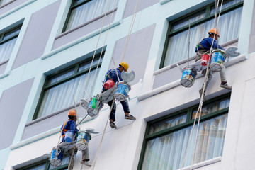 Worker are painting the color in high rise buildings.