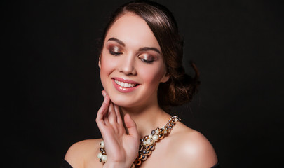 beautiful smiling woman with perfect makeup wearing jewelry