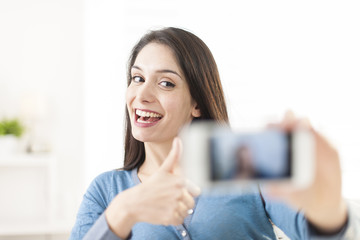 beautiful young woman taking a selfie with her smartphone