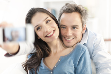 cheerful couple taking a selfie with a smartphone