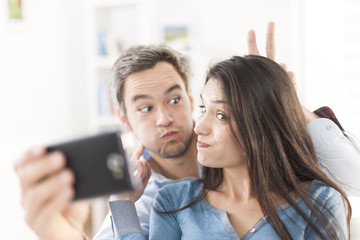 cheerful couple taking a humoristic selfie with a smartphone