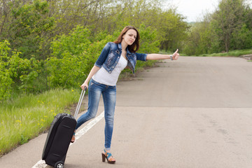 Woman with a suitcase thumbing a lift