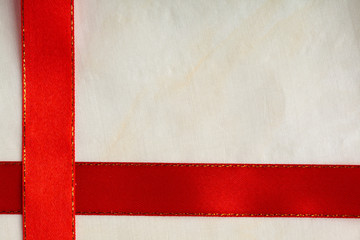 Shiny red ribbon stripe on bright cloth background.